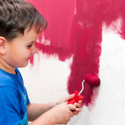boy painting the wall red
